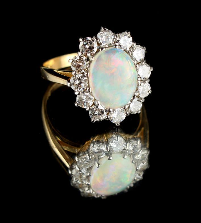 5b8dec1e605d08 An 18ct yellow gold opal & diamond cluster ring, the centre oval opal  weighing approximately 1.05 carats,